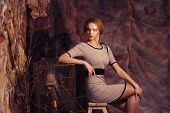 picture of stool  - young fashion model sitting on a stool in drama decoration - JPG