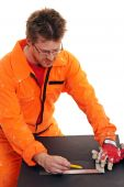 Arbeiter in orange Workwear Messen mit einem Lineal