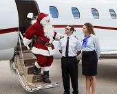 Santa thanking pilot and airhostess while disembarking private jet at airport terminal
