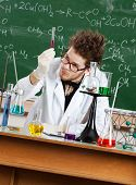 Mad professor examines a beaker in his laboratory