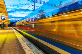 foto of passenger train  - Railroad travel and transportation industry business concept: summer evening view of high speed commuter passenger train departing from railway station platform with motion blur effect ** Note: Slight blurriness, best at smaller sizes - JPG