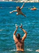 Father Throwing Baby Over The Water