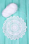 White yarn for knitting with napkin and spokes on wooden table close-up