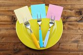 Empty note papers attached to forks, on plate, on color wooden background