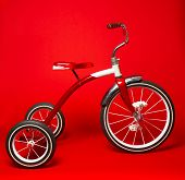 image of tricycle  - A vintage red tricycle on a bright red background - JPG