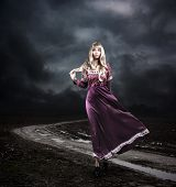 stock photo of flutter  - Full Length Portrait of Fantasy Woman in Waving Purple Dress Walking on Dirty Road - JPG