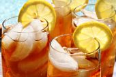 stock photo of iced-tea  - Four glasses of lemon ice tea outside by the pool - JPG