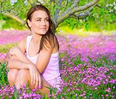 Portrait of beautiful calm girl sitting down on pink floral glade under blooming apple tree, relaxat