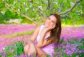 Portrait of nice dreamy girl sitting down on pink flowers field in apple tree garden, watching for f