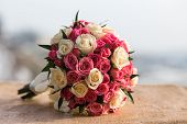 stock photo of marriage ceremony  - Wedding bouquet of red white roses lying on a stone - JPG