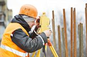 picture of theodolite  - One surveyor worker working with theodolite transit equipment at road construction site outdoors - JPG