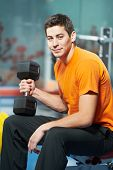 stock photo of triceps brachii  - Smiling athlete man at biceps brachii muscles exercises with training dumbbells in fitness gym - JPG