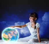 Cute girl sitting in bed and looking at Earth planet. Elements of this image are furnished by NASA
