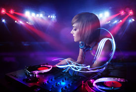stock photo of disc jockey  - Pretty young disc jockey girl playing music with light beam effects on stage - JPG