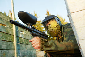 foto of paintball  - paintball player in prootective uniform and mask aiming and shoting with marker outdoors - JPG