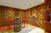 picture of wine cellar  - Wine cellar interior in basement room with decorative wooden barrel and two red high chairs - JPG
