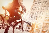 picture of pedal  - Man on bike in traffic with sunflare - JPG