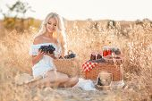 foto of carnal  - Beautiful blond woman enjoying a warm summer day sitting in a meadow with a brush of ripe grapes in his hand. ** Note: Visible grain at 100%, best at smaller sizes - JPG