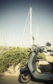 stock photo of sparring  - vintage green scooter in the harbour with spars in background - JPG