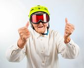 stock photo of grandma  - funny grandma wearing a yellow bicycle helmet and ski goggles and showing thumbs up - JPG