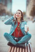 stock photo of hot pants  - Young beautiful hipster girl drinking coffee in the city - JPG