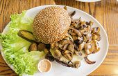 picture of sauteed  - A dish with a hamburger with sauteed mushrooms on top sesame bun bread letuce and mayonaise. A delicious grilled burger a junk food meal. ** Note: Soft Focus at 100%, best at smaller sizes - JPG