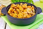 stock photo of jerusalem artichokes  - Jerusalem artichokes roasted in a roasting pan fresh tubers on a napkin parsley vegetable oil on a background of white wooden plank - JPG
