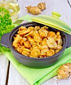 stock photo of jerusalem artichokes  - Jerusalem artichokes roasted in a roasting pan with a lid fresh tubers of on a napkin parsley vegetable oil on a background of white wooden plank - JPG