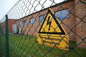 stock photo of voltage  - High voltage sign on a fence in Germany - JPG