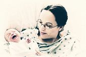 image of baby delivery  - A new mother holds her crying newborn baby. Filtered to give vintage faded look. ** Note: Visible grain at 100%, best at smaller sizes - JPG