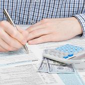 stock photo of cpa  - Male filling out 1040 US Tax Form with calculator and 100 dollars next to it - JPG