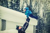 foto of throw up  - An image captures a happy father throwing his smiling baby son up in the air during a snowfall in the winter season - JPG