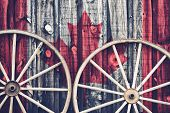 picture of red siding  - A close up of two antique wagon wheels lying up against a building with wooden siding depicting the flag of Canada on its surface - JPG