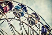 picture of amusement park rides  - Background image of a close up low angle view of ferris wheel passenger cars high up against a cloudy sky at an amusement park - JPG
