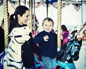 picture of carnival ride  - A happy mother and son are riding on a carousel together smiling and having fun at an amusement park - JPG