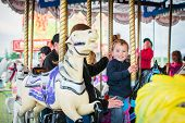 stock photo of amusement park rides  - An excited young boy sits on a horse on a carousel as the ride starts in an amusement park - JPG