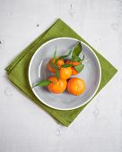 foto of clementine-orange  - Clementine tangerines with green leaves on white wooden background in a grey bowl - JPG