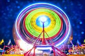 foto of ferris-wheel  - A ferris wheel taken at night using a long exposure to capture the circular motion of the lights - JPG