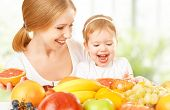 foto of healthy eating girl  - happy family mother and daughter little girl eat healthy vegetarian food lots of fruit - JPG