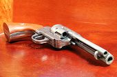 image of revolver  - A replica of an old .44 six shooter revolver on a wooden cabinet ** Note: Shallow depth of field - JPG