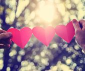 image of sweethearts  - hands holding a string of paper hearts up to the sun during sunset toned with a retro vintage instagram filter effect - JPG