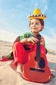 picture of ukulele  - Toned photo of Little happy smiling boy plays his guitar or ukulele - JPG