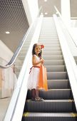 stock photo of mall  - Happy little girl with shopping bag in the mall - JPG