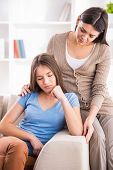 foto of depressed teen  - Mother and teen daughter after quarrel on sofa at home - JPG