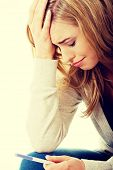 stock photo of pregnancy  - Sad young woman holding pregnancy test feeling hopeless - JPG