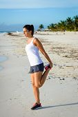picture of trans  - Sporty woman stretching legs after running at tropical beach during caribbean vacation - JPG
