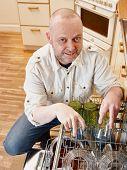 foto of dishwasher  - Homeworking smiling man fills up the dishwasher - JPG
