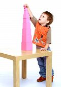 pic of montessori school  - Serious little boy collects Red Pyramid in the Montessori school - JPG