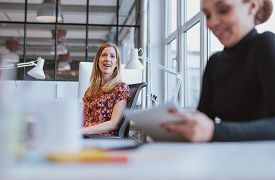 picture of chat  - Happy young woman having a friendly chat with her female colleague while at work - JPG