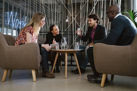 stock photo of coworkers  - Multiracial business team sitting in office lobby discussing new business ideas - JPG